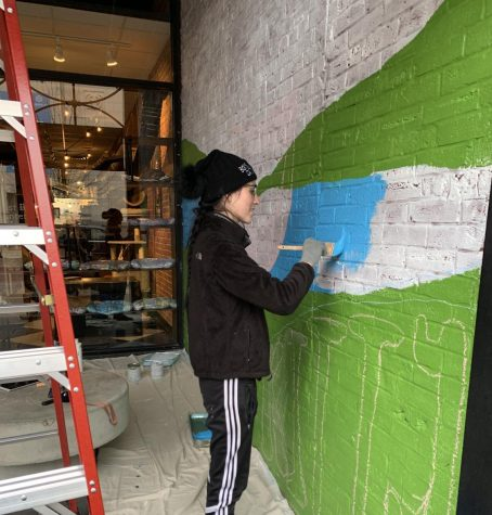 Jenna Sharp, USI graduate and recipient of the Endeavor Award grant, paints a mural at the River Kitty Cat Cafe on Main Street.