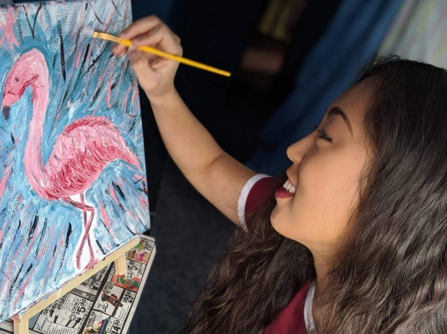 Graduate Cailan Walters paints a flamingo in her room April 4. Walters said she is spending her newly found free time doing new hobbies.