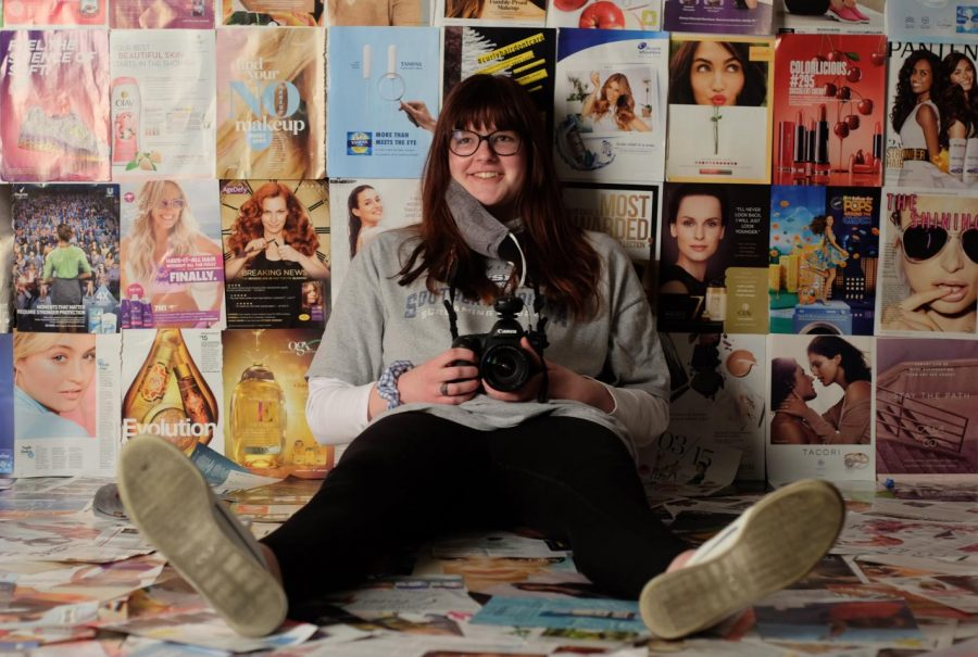 photographer, Megan Thorne, sits in front of her custom background