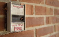 a fire alarm against a brick wall