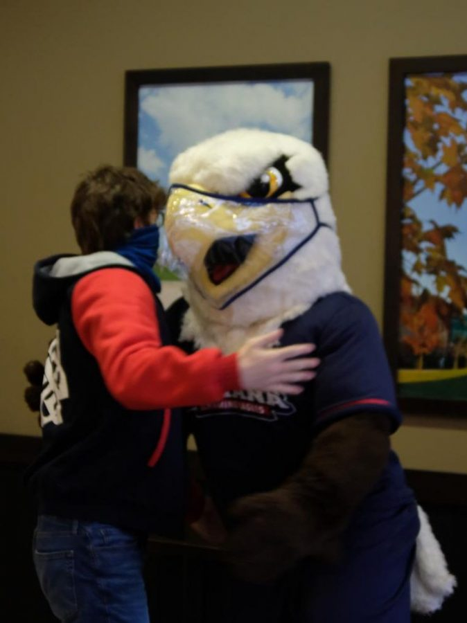 Ethan Wakeman, junior communication studies major,  reaches in to hug a masked up Archie in the university Jazz Lounge, Tuesday.