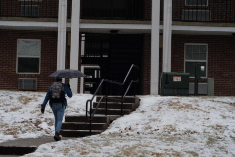 A student walks through snow and ice near university housing