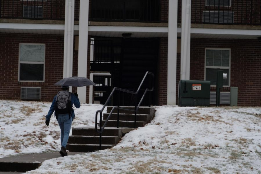 A+student+walks+through+snow+and+ice+near+university+housing