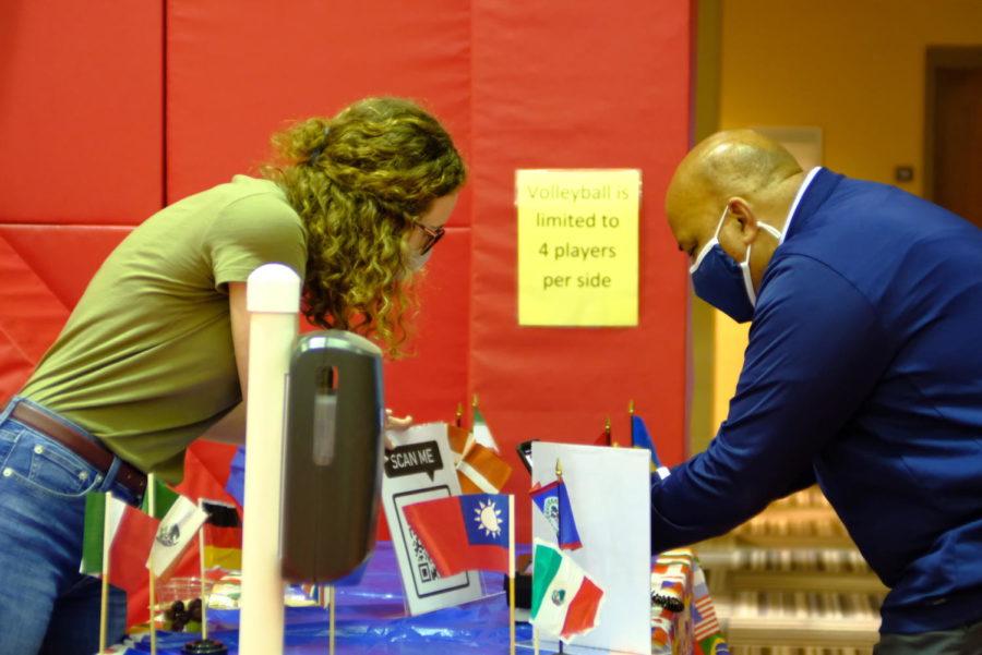 Hannah Payne, sophomore English major, helps President Rochon sign into the International Festival Friday.