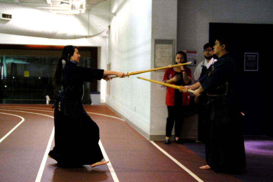 Tamura and Komatsu spar with bamboo swords in the upper level of the Recreation Fitness & Wellness Center. The swords they are using are called shinai which comes from the Japanese verb shinau, meaning to bend or flex.