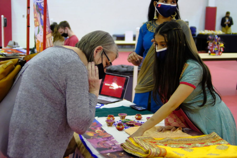 Netra Patel, freshman nursing major, shows an attendee the traditional fabrics and celebrations of India. She points to a photograph of the festival of colors, a Hindu celebration practiced around the world.