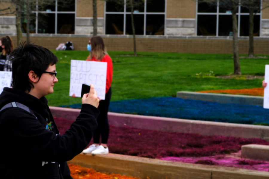 Isabella Cochran, freshman biology major, takes a photo of the demonstration in front of David L. Rice Library Wednesday.