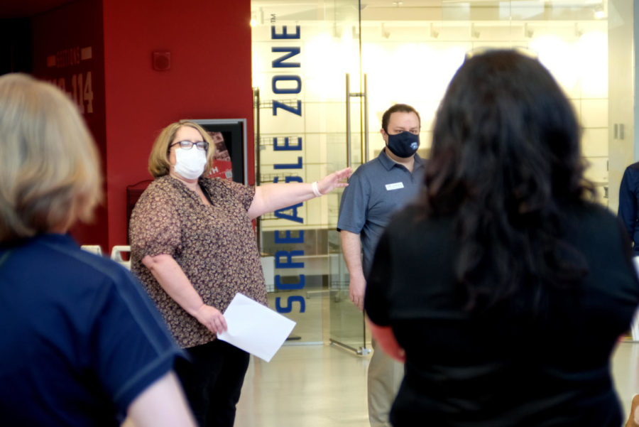 Brandy Sitzman, practice manager for the university Health Center, briefs volunteers in the lower level of the Screaming Eagles Arena Wednesday. The volunteers helped students check into the clinic and directed them where to go.