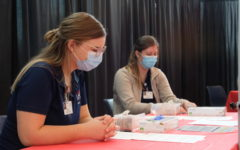 Nursing students Eleanor Conley and Maddison Fields prepare their vaccination stations Apr. 7. Conley said it was an honor to administer COVID vaccines to her fellow students.