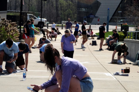 Greek life students work on murals for the Chalk Mural Contest by the Fuquay Welcome Center. Teams receive points from the contest that go toward their fraternity or sorority for Greek Week.