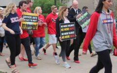 James Beeby, dean of the College of Liberal Arts, walks in red high-heels with other male students as part of Walk a Mile in Her Shoes, April 11, 2017. This year, the annual event will be replaced with a silent demonstration in front of the David L. Rice Library.