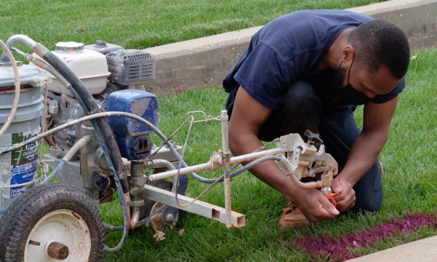 Worker Julian Miller fixes the nozzle of a paint sprayer outside the David L. Rice Library. The steps outside the library are painted annually to celebrate Spring Fest.