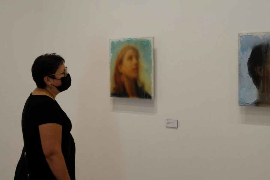 Adjunct professor Erika Anderson views one of the frescos by Mike Nichols in the McCutchan Art center Sept. 9. This series by Nichols is different than his previous work because they are airbrushed rather than being painted.