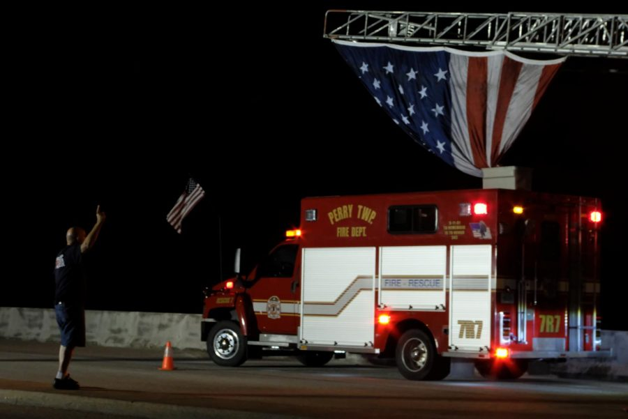 Jerry Bulger, former fire chief for Perry Township, signals the crane operators to raise the flag over the Lloyd Expressway at the stroke of midnight.