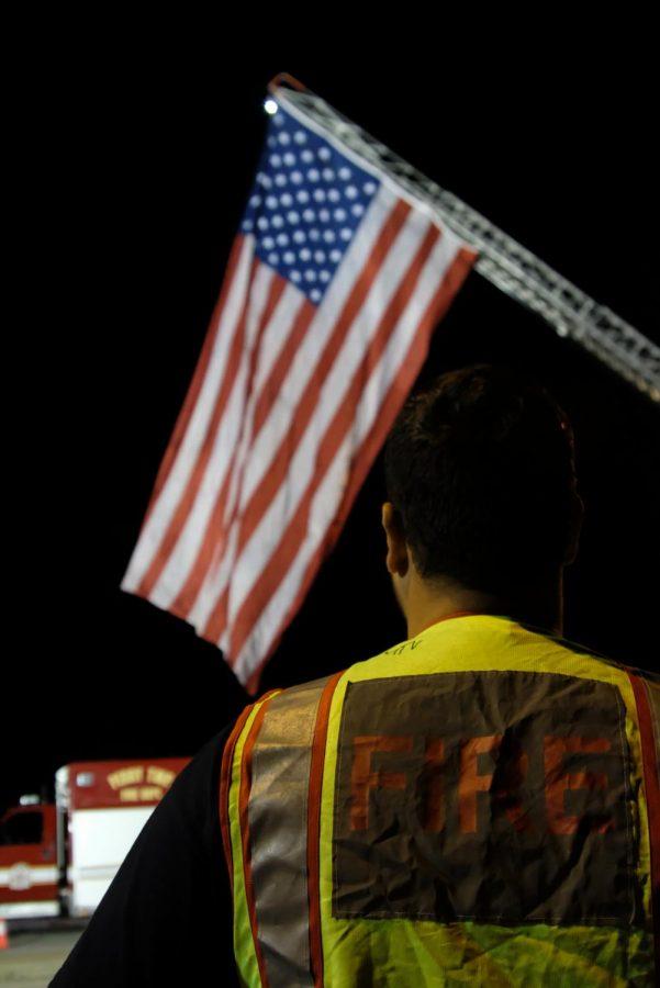 Tarek Khaja, volunteer firefighter and university public saftey officer, looks at the raised flag across the four lanes on University Parkway. He has been a volunteer firefighter for New Harmony for four years.