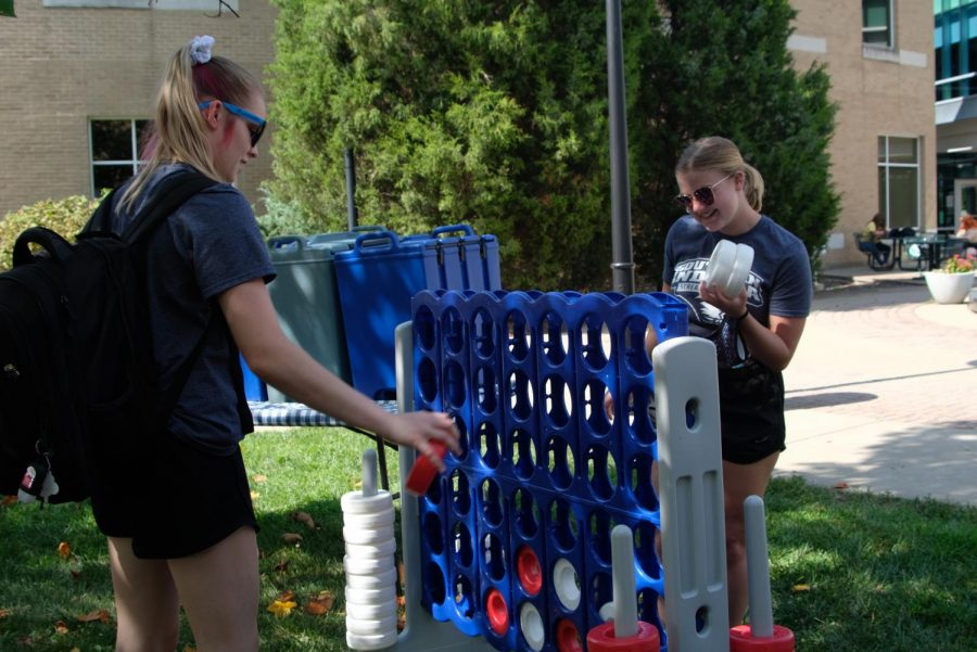 Gabby Eagleson, freshman Biology major, and Ali Boilanger, Freshman Nursing major, play a game of connect four next to the booth hosted by the Center for Campus Life.