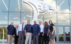 David Bower, Joan Kempf deLong, Tim Mahoney, Zane Mitchell, Ronald Rochon, Jon Mark Hall, Khalilah Doss and Kindra Strupp stand in front of the sculpture at the Screaming Eagles Complex.  President Rochon called it a photo for the archives as they gathered around the statue.