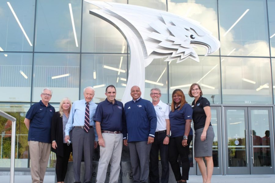 David Bower, Joan Kempf deLong, Tim Mahoney, Zane Mitchell, Ronald Rochon, Jon Mark Hall, Khalilah Doss and Kindra Strupp stand in front of the sculpture at the Screaming Eagles Complex.  President Rochon called it a