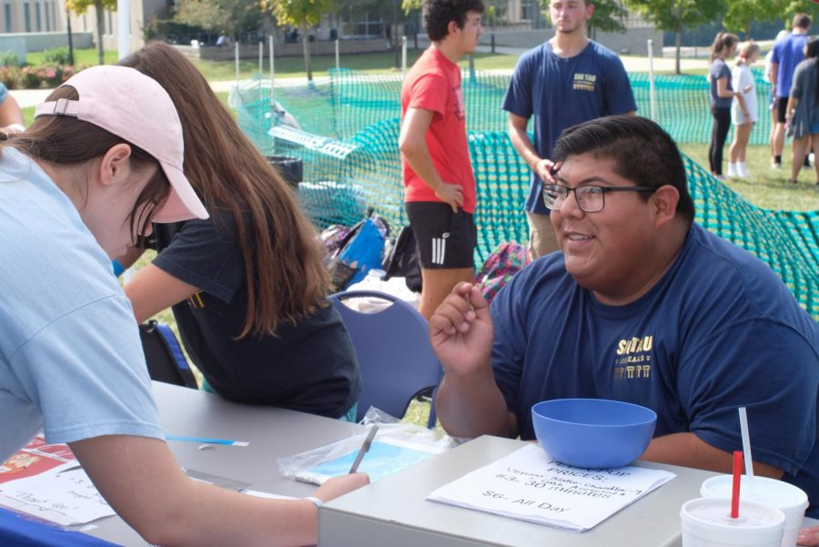Hairo Rivas, president of Sigma Tau Gamma, asks an attendee to sign in for contact tracing. Over 200 students attended the Pet-A-Pup event Wednesday.