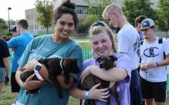 Simrin Singh, a senior communications major, and Elizabeth Angermeier, a sophomore nursing major both cuddle up to some pups at Sigma Tau Gammas Pet-A-Pup event on Wednesday. The puppies are both ten weeks old and are available for adoption.