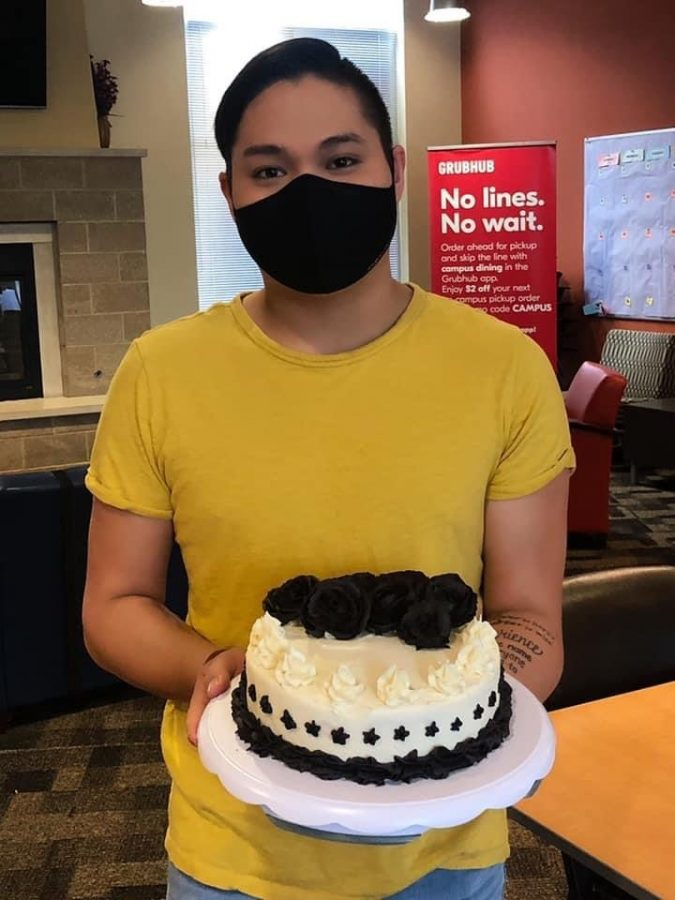 Tyler Hagen holds his award winning cake that won the university baking competition in April. Hagen hand-pipped the buttercream roses on to a homemade vanilla cake.