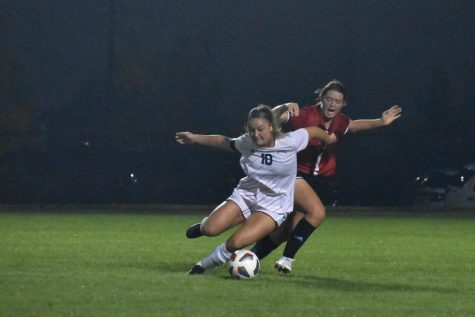 Senior defender Madeline Weston prepairs to kick the ball followed closely by a Maryville player.