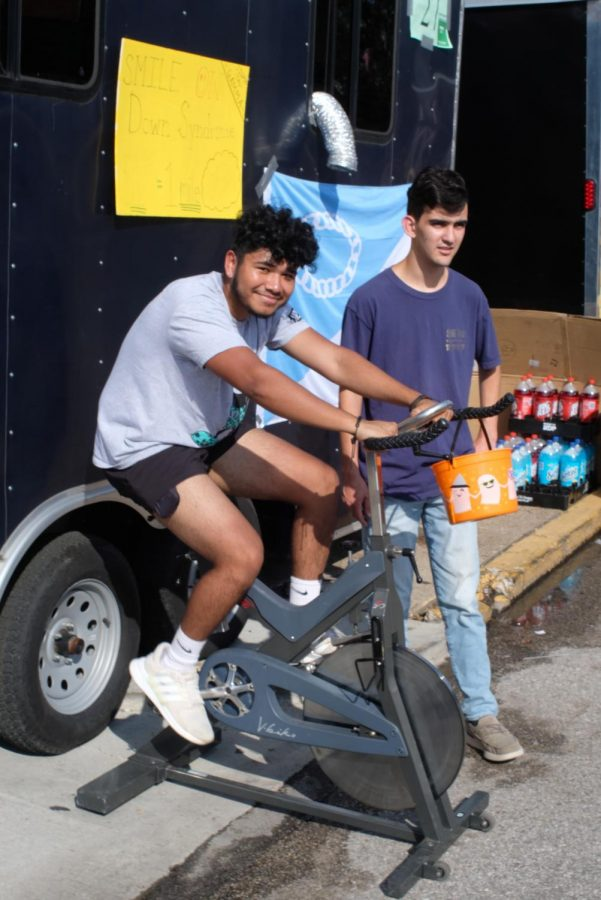 Members of Sigma Tau Gamma fraternity, Gilberto Sanchez, and Shane Seessengood, take turns on the stationary bike outside their booth Tuesday. If the seat was more comfortable it would be a lot easier, Sanchez said. For every dollar donated to the Special Olympics he rides an additional mile.