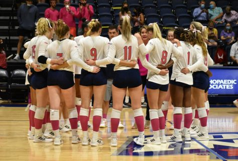 Womens volleyball team wears pink Friday for the Breast Cancer Awareness Match. The players, coaches and fans sported pink for the cause.