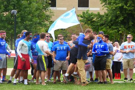 The brothers of Sigma Tau Gamma welcome a new member during Fraternity Bid Day at Rice Library Friday, during which 93 university men received bids from their new fraternity.