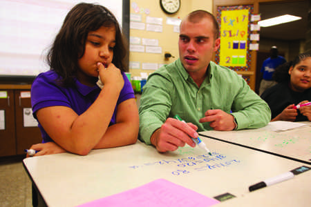 Helping Lodge Elementary student Emily Myers, senior elementary education major Austin Chamberlain goes through different multiplication problems with his fifth grade students. Chamberlain visits this classroom daily as a part of the Pilot Education Program.