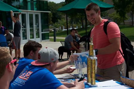 Freshman Tyler Kirk, business administration, listens to President Tanner Gellinger, criminal justice senior, talk about the benefits of joining the Kappa Alpha Fraternity while tabling outside the UC Friday.