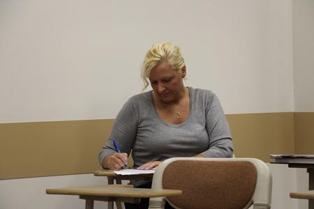 Mandi Fulton, the assistant athletics director, grades her student's presentation during a public speaking class that she teaches.