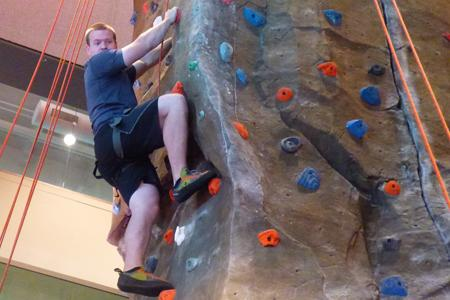 Brandon Becker, a junior majoring in geology, climbs the rock wall in the RFWC.