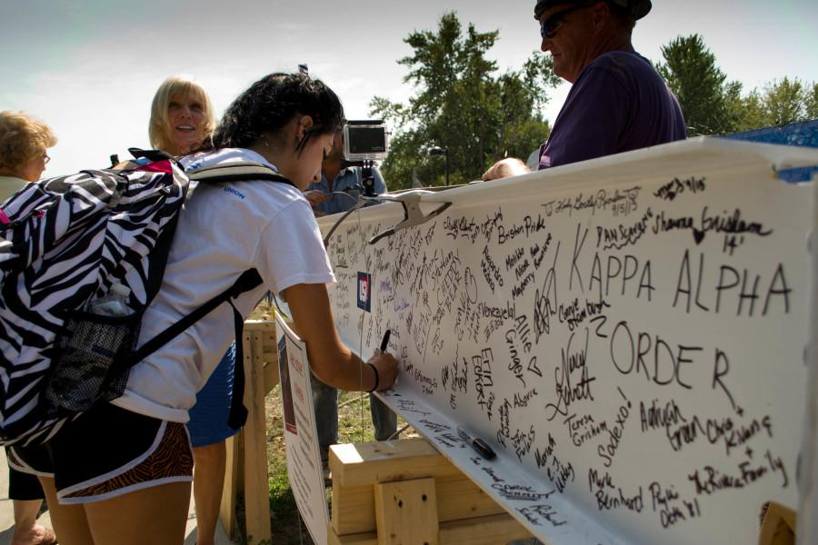 Skyela Hughes signs the beam before it is placed on the Teaching Theatre Thursday.  Photo by NIGEL MEYER/The Shield