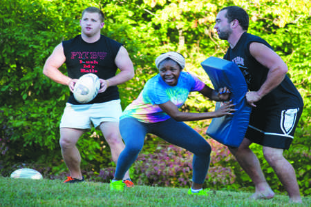 Freshman psychology major Dajha Brown works on a drill at the rugby practice on Tuesday. Coach Tyler Pipes and Assistant Coach Adam Kunkel man the drill before sending the team off to run laps. Brown was one of two women at the practice who are working to put together a women's rugby club sport.